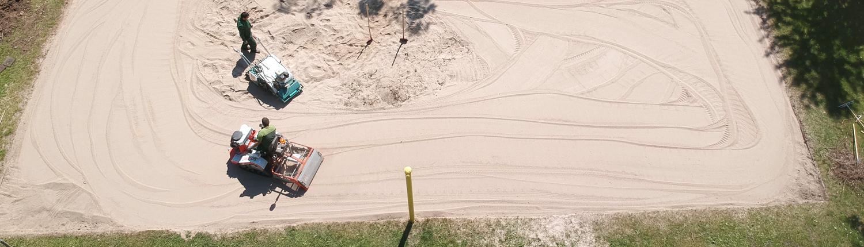 Ein Beachvolleyballfeld wird gereinigt mit Maschinen